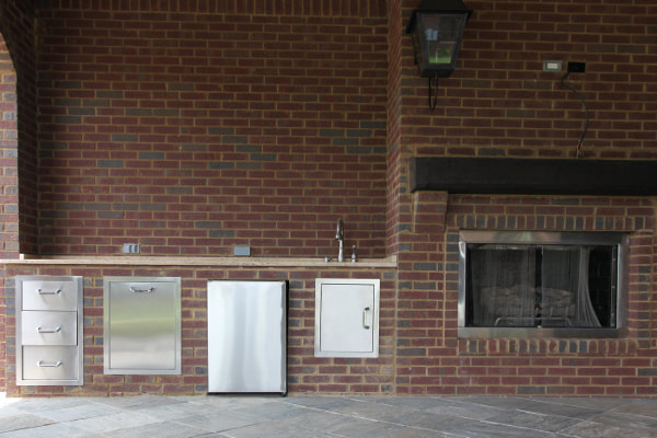 Brick outdoor kitchen with stainless steel appliances and fireplace