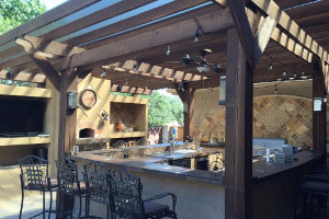 Outdoor kitchen with bar and wood pergola cover