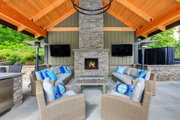 Wood ceiling patio with stacked stone fireplace and stone accent surround walls