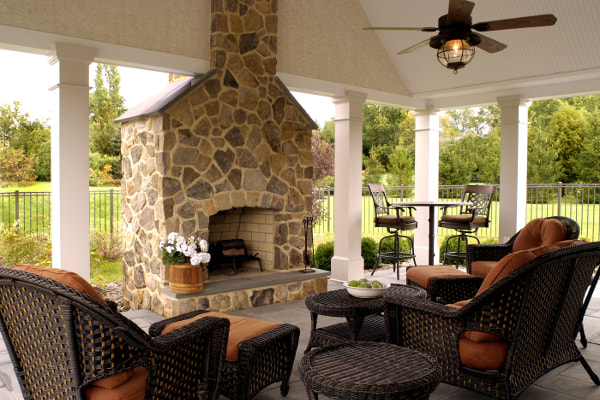Outdoor stone masonry fireplace in covered patio